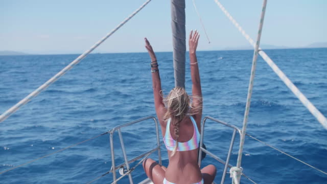 woman in a rainbow swimsuit swimwear bikini on the bow of a sailboat boat while sailing in greece. - blondes haar stock-videos und b-roll-filmmaterial