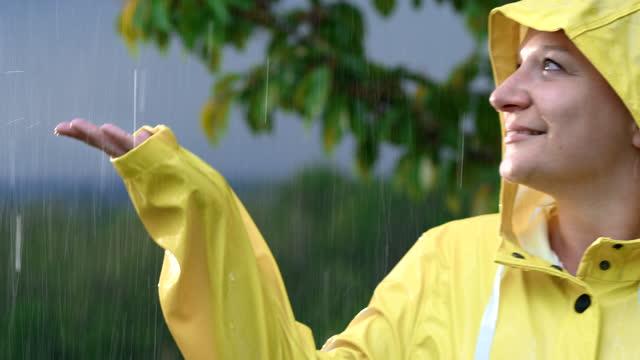 slo mo frau im regenmantel und genießt den regen - gelb stock-videos und b-roll-filmmaterial