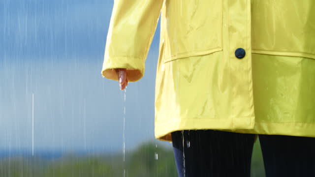 slo mo frau im regenmantel im regen - gelb stock-videos und b-roll-filmmaterial