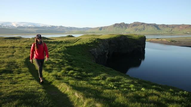 a woman in a red jacket hiking a path through a lush green field. - solo una donna di età media video stock e b–roll