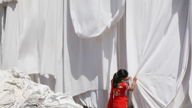vidéos et rushes de a woman in a red sari stretches freshly dyed fabrics hanging out to dry. - dry clothes