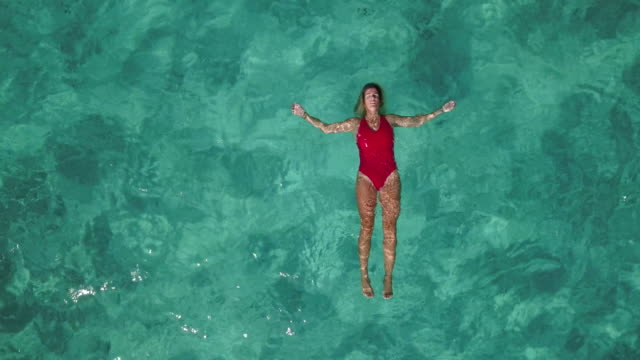 AERIAL, ZO A woman in a red swimsuit floats in clear blue water