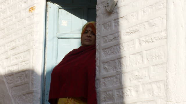 a woman in a sari stands in a doorway. - bindi stock videos and b-roll footage