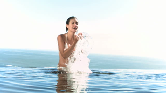 Woman splashing water on her face in slow motion