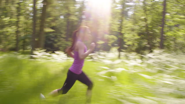 TS Woman in a violet top running through the forest