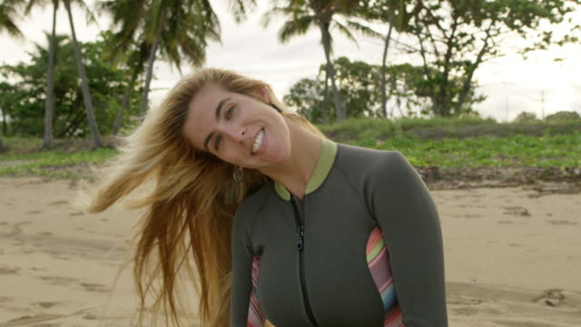 MS A woman in a wetsuit smiles to camera