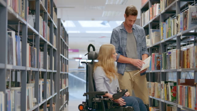 Woman in a wheelchair browsing through books with a friend in the library