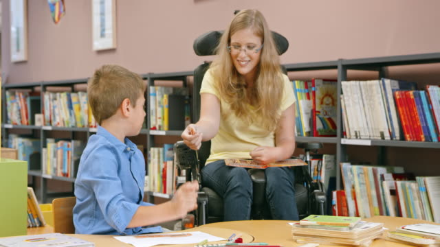 DS Woman in a wheelchair handing crayons to a little boy drawing in the library