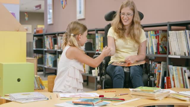 DS Frau im Rollstuhl Umgang mit Buntstifte für Mädchen in der Bibliothek