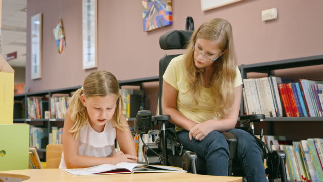 ds woman in a wheelchair listening to a girl reading in the library - disability stock videos and b-roll footage