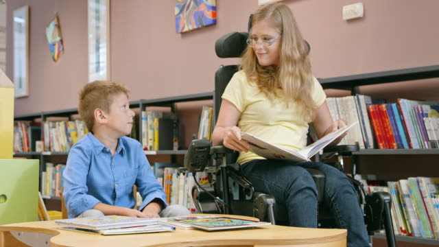 DS Woman in a wheelchair reading to a young boy in the library