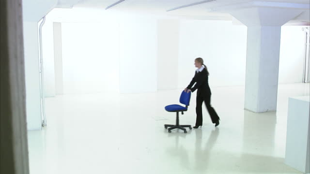 a woman in a white and empty office premises sweden. - chair stock videos and b-roll footage