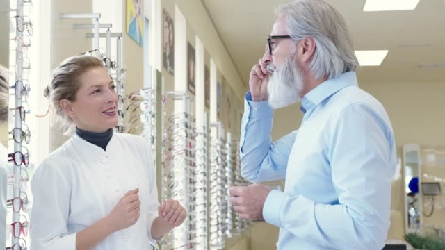 woman in a white coat working in optics shop helping a senior man with beard pick his new glasses - optometrist stock videos & royalty-free footage
