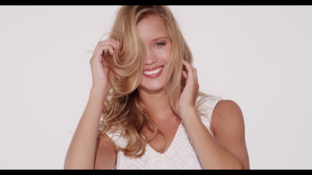 vidéos et rushes de a woman in a white dress smiles and plays with hair - beauty