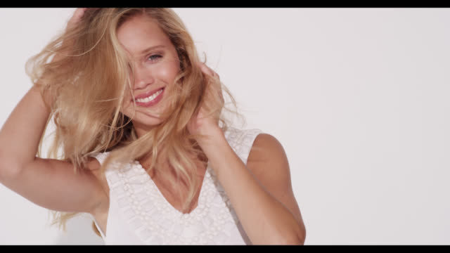 vidéos et rushes de a woman in a white dress smiles with hair blowing around - cheveux blonds
