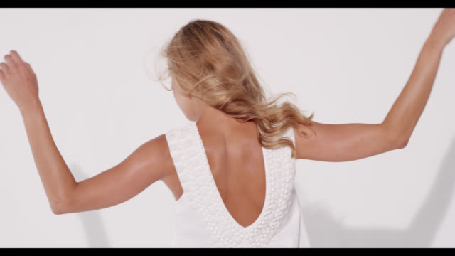 a woman in a white dress spins around and smiles - urbanlip stock videos & royalty-free footage