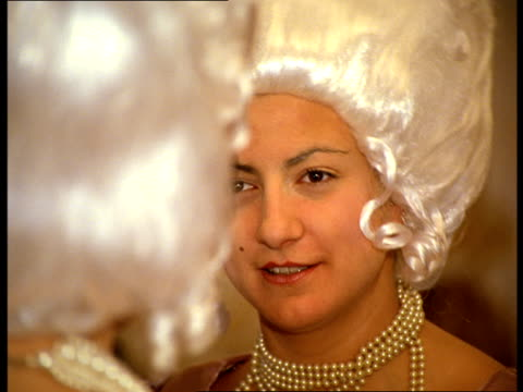 vídeos de stock, filmes e b-roll de a woman in a white wig with a pierced tongue laughs and talks with another woman. - 18th century