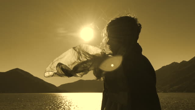 woman in a windy day and her hair and scarf is moving with sunlight in sepia toned - sepia stock videos & royalty-free footage