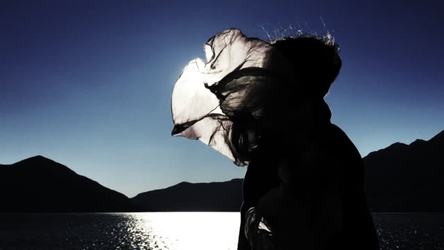 Woman in a Windy Day and Her Hair and Scarf is Moving with Sunlight