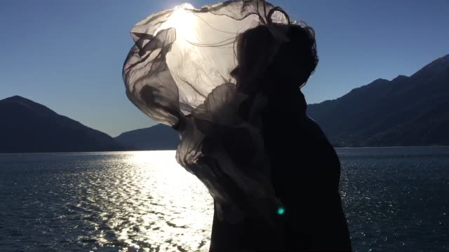 woman in a windy day and her hair and scarf is moving with sunlight - produced segment stock videos & royalty-free footage