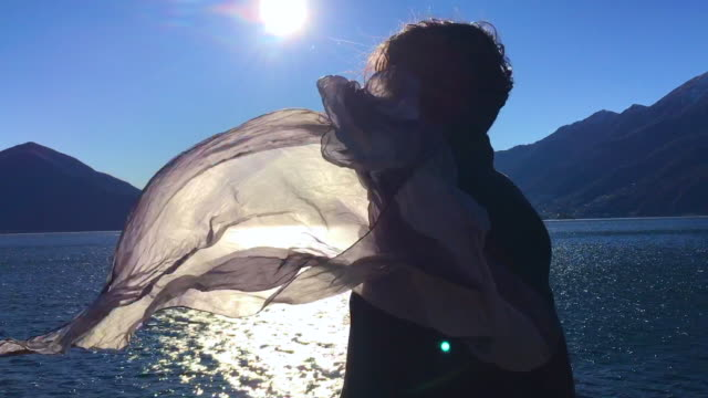 woman in a windy day and her hair and scarf is moving with sunlight - mid length hair stock videos & royalty-free footage