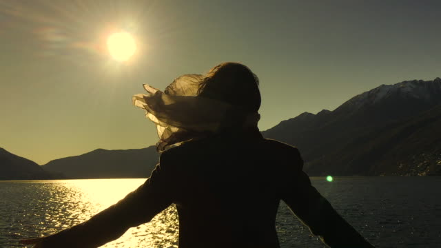woman in a windy day with a scarf in rear view arms outstretched against alpine lake with mountain and sunlight - back lit woman stock videos & royalty-free footage