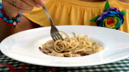 Woman in a yellow dress is eating a pasta with white sauce.