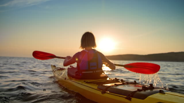 slo mo woman in a yellow sea kayak passing by on the water at sunset - kayak video stock e b–roll