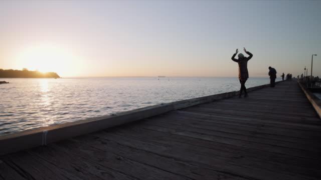 A woman in a yoga pose at sunset, Mornington Peninsula, Victoria, Australia