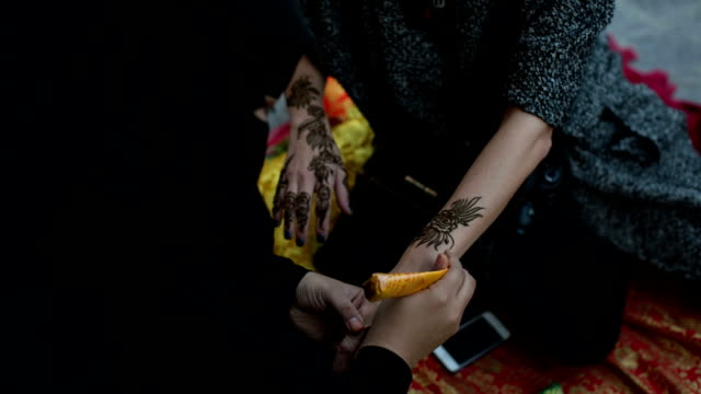 a woman in abaya gets a henna tattoo on the arm at the arabian market souq waqif in doha, qatar - souk stock videos & royalty-free footage