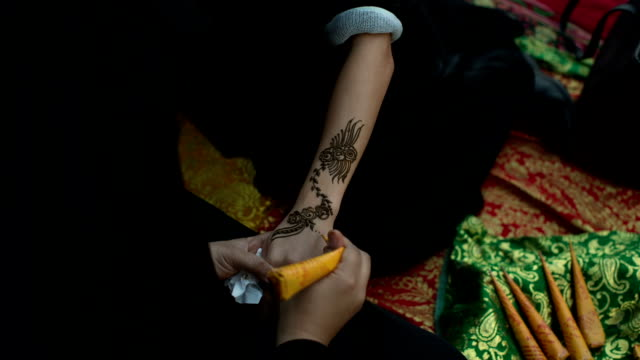a woman in abaya gets a henna tattoo on the arm at the arabian market souq waqif in doha, qatar - traditional clothing stock videos & royalty-free footage