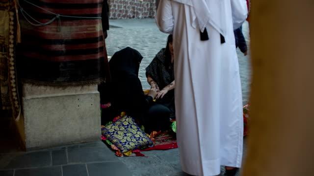 stockvideo's en b-roll-footage met a woman in abaya gets a henna tattoo on the arm at the arabian market souq waqif in doha, qatar - doha