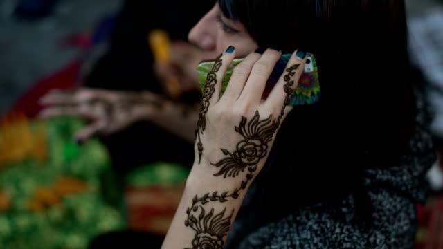 vidéos et rushes de a woman in abaya gets a henna tattoo on the arm at the arabian market souq waqif in doha, qatar - qatar