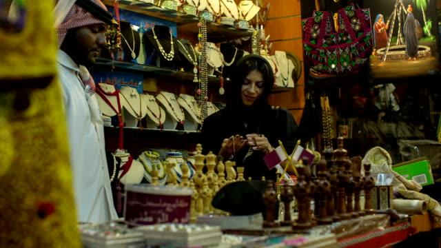 A woman in abaya grubs in a souvenir shop at the Arab market in Doha, Qatar.