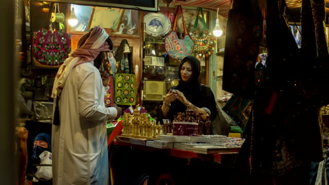 a woman in abaya grubs in a souvenir shop at the arab market in doha, qatar. - doha stock videos & royalty-free footage