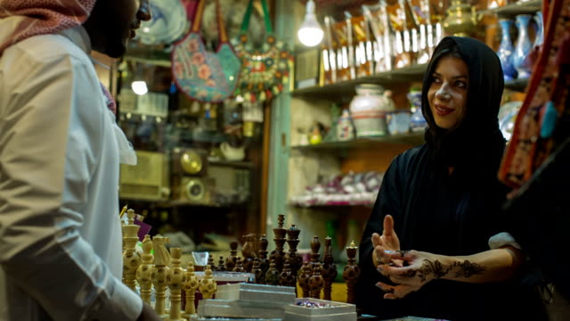 a woman in abaya grubs in a souvenir shop at the arab market in doha, qatar. - souk stock videos & royalty-free footage