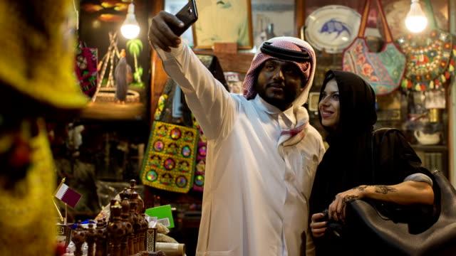 a woman in abaya grubs in a souvenir shop at the arabic market in doha, qatar. - qatar stock videos & royalty-free footage