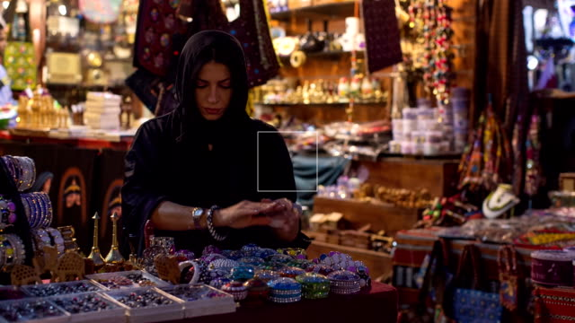 a woman in abaya grubs in a souvenir shop at the arabic market in doha, qatar. - souk stock videos & royalty-free footage