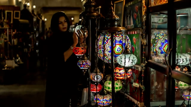 A woman in abaya grubs in a souvenir shop at the Arabic market in Doha, Qatar.