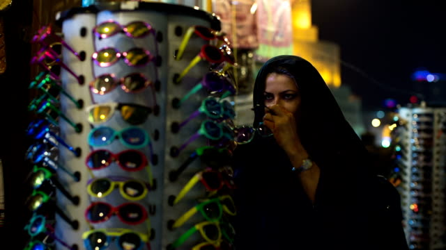 a woman in abaya looks for sun glasses at the arabian market souq waqif in doha, qatar. - sunglasses stock videos & royalty-free footage