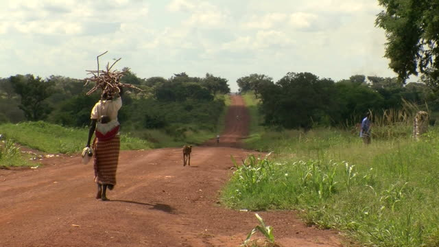 woman in africa walking down dirt road