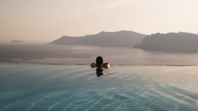woman in an infinity pool overlooking the mediterranean - oia santorini stock videos & royalty-free footage