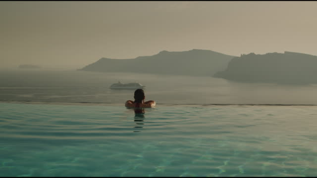 woman in an infinity pool - oia santorini stock videos & royalty-free footage