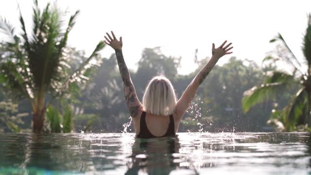 腕を上げたインフィニティプールの女性 - インフィニティプール点の映像素材/bロール