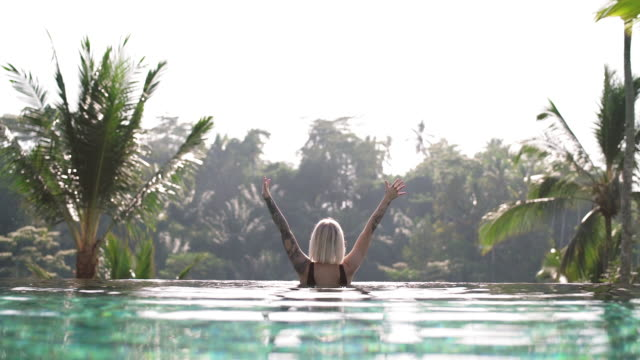 woman in an infinity pool with her arms raised - idyllic stock videos & royalty-free footage