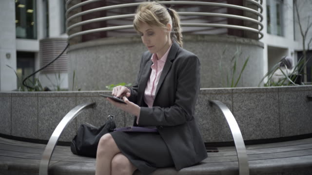 A woman in an urban environment browsing her computer tablet