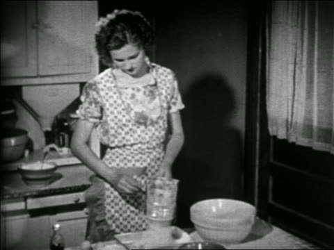b/w 1938 woman in apron sifting flour in kitchen / educational - stay at home mother stock videos & royalty-free footage