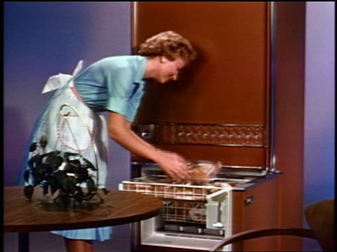 1959 woman in apron taking frozen TV dinners from freezer in kitchen / industrial