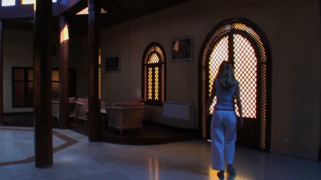 woman (シルエット)がアラビアンホールはガラスドアを閉鎖いたします。 - ロビー点の映像素材/bロール