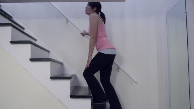 Woman in athletic clothes and knee pain walking up home stairs.